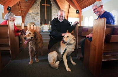 MONTREAL, QUEBEC; MARCH 28, 2013 -- Sandy and Ian Temple and their dogs Toby, left and Myles flank Archdeacon Michael Johnson at Christ Church Beaurepaire in Beaconsfield, west of Montreal Thursday, March 28, 2013. The church offers a monthly service called Paws & Pray to which parishioners can bring their dogs. (John Mahoney/THE GAZETTE)